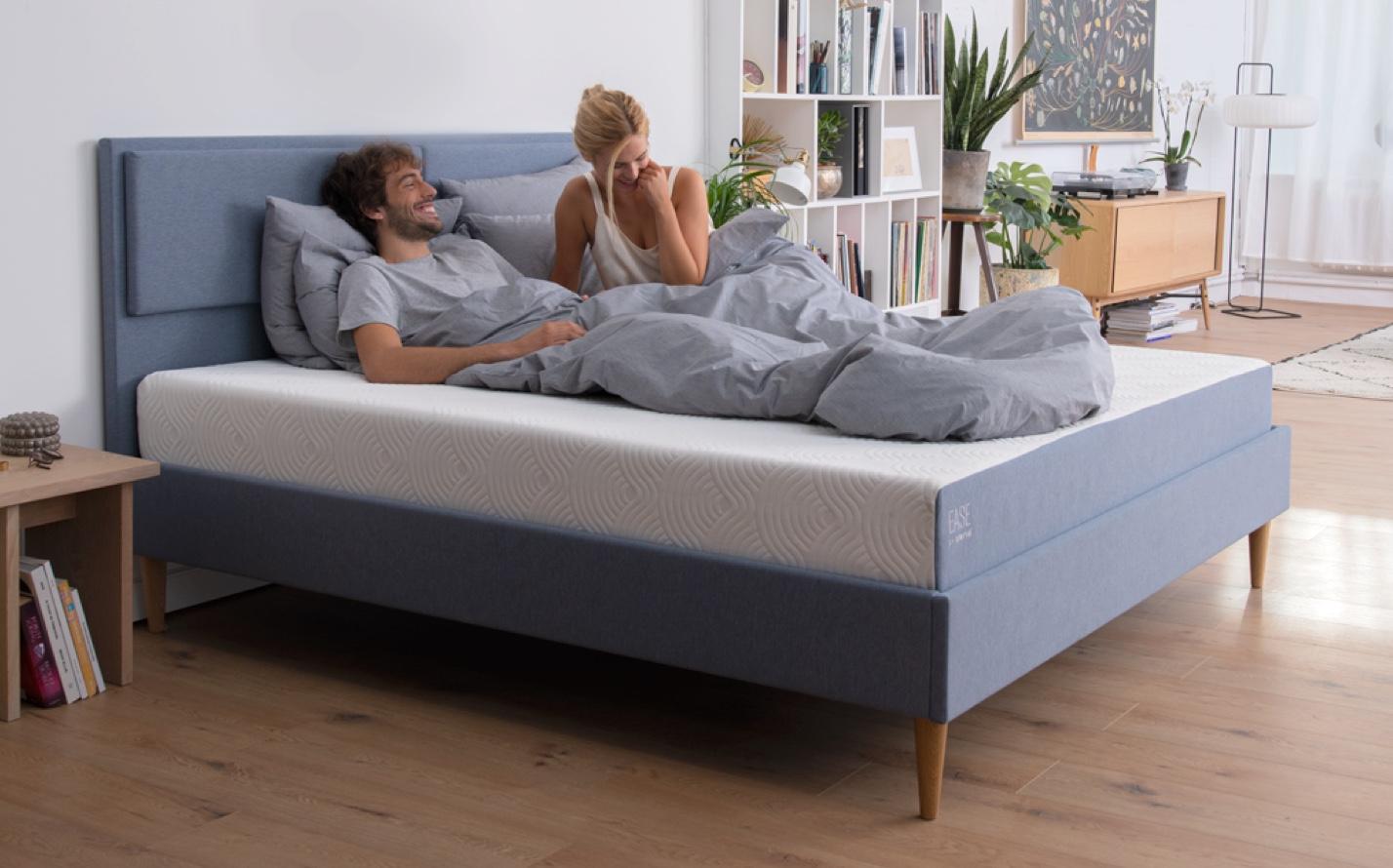 para rozmawia siedząc na łóżku pod pościelą na materacu EASE BY TEMPUR