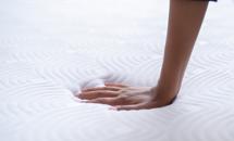 ręka naciska materac Tempur pokazując jak materac odkształca się tylko w miejscu nacisku