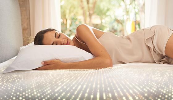 Kobieta na łóżku i poduszce marki Tempur