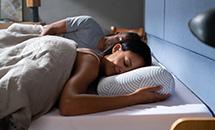 kobieta leży na łóżku na brzuchu z głową bokiem na poduszce Tempur