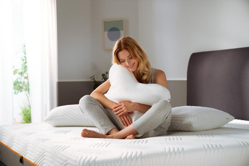 Kobieta na łóżku z poduszką marki Tempur