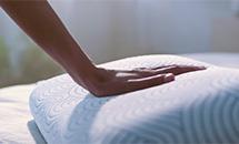 ręka delikatnie naciska poduszkę Tempur z lewej strony