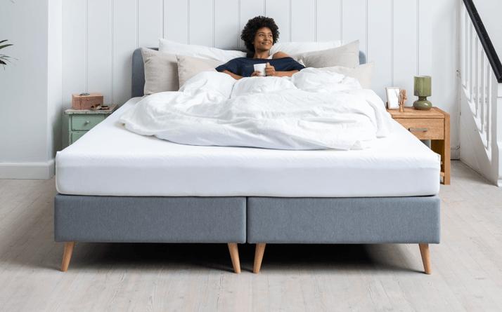 uśmiechnięta młoda kobieta siedzi oparta o poduszki pod pościelą na łóżku z materacem Tempur i trzyma kawę